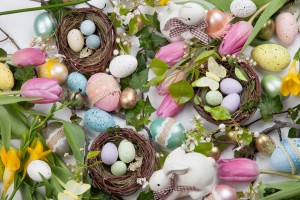 Close up of Easter assortiment of Easter eggs, spring flowers, and toys over white background